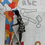 Akouvi all'opera sul mural dell'école catholique