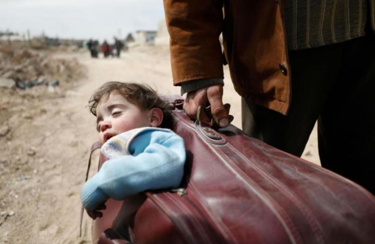 Siria: la foto del bimbo in valigia che fugge dalla guerra ha fatto il giro del mondo